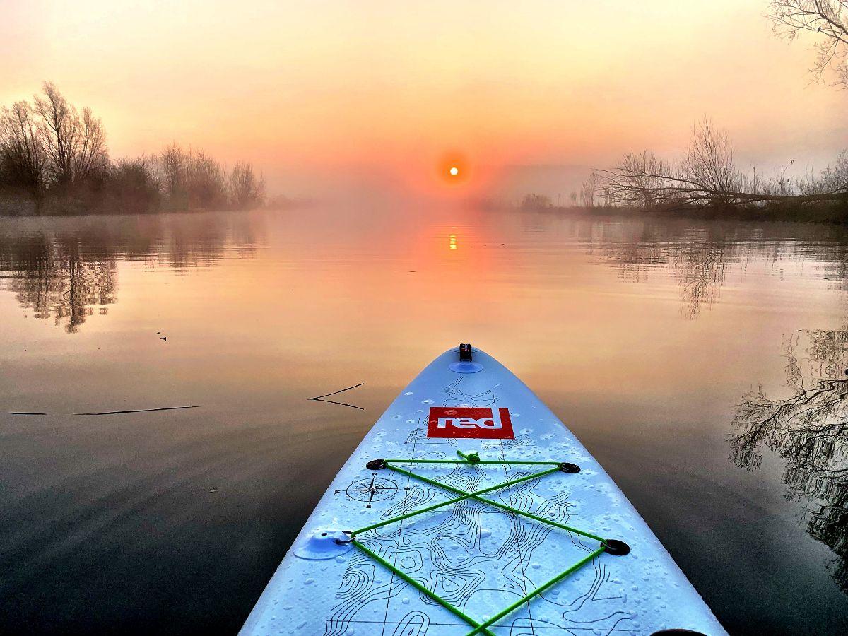 Het voorste deel van een SUP-board op de rivier met laaghangende mist en de zonsopkomst