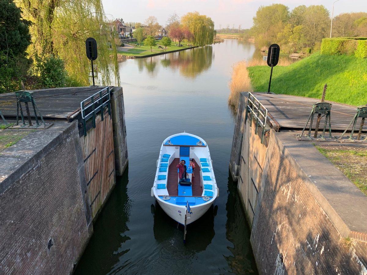 Een man in een boot die een sluis in vaart, in de achtergrond een vergezicht naar de rivier