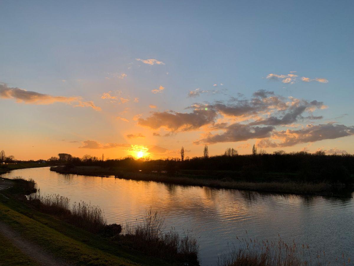 Enkele wolken in een blauwe lucht met een gouden zonsondergang met op de voorgrond een rivier die in de verte een bocht omgaat