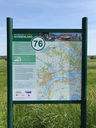 Routekaart op informatiebord met informatie op de achtergrond gras en lucht met sluierbewolking