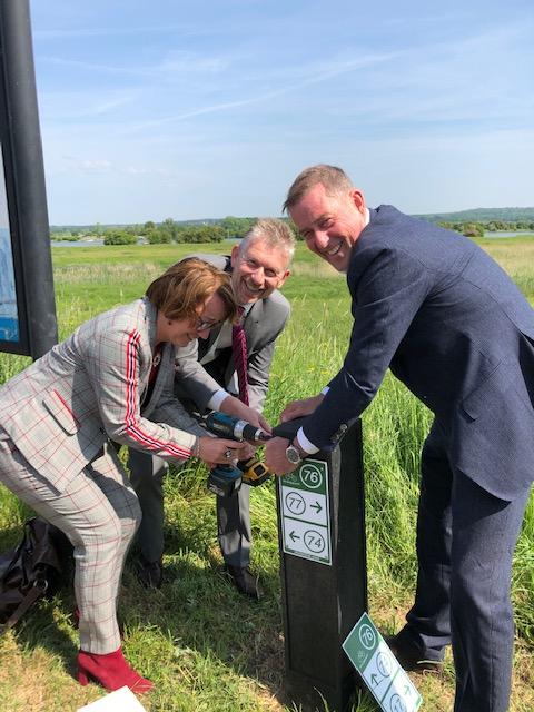 Gedeputeerde Bea Schouten bevestigt met accuschroefmachine een bordje aan een paaltje dat wordt vastgehouden door burgemeester De Boer en directeur Uiterwaarde. Op de achtergrond gras en lucht met sluierbewolking.