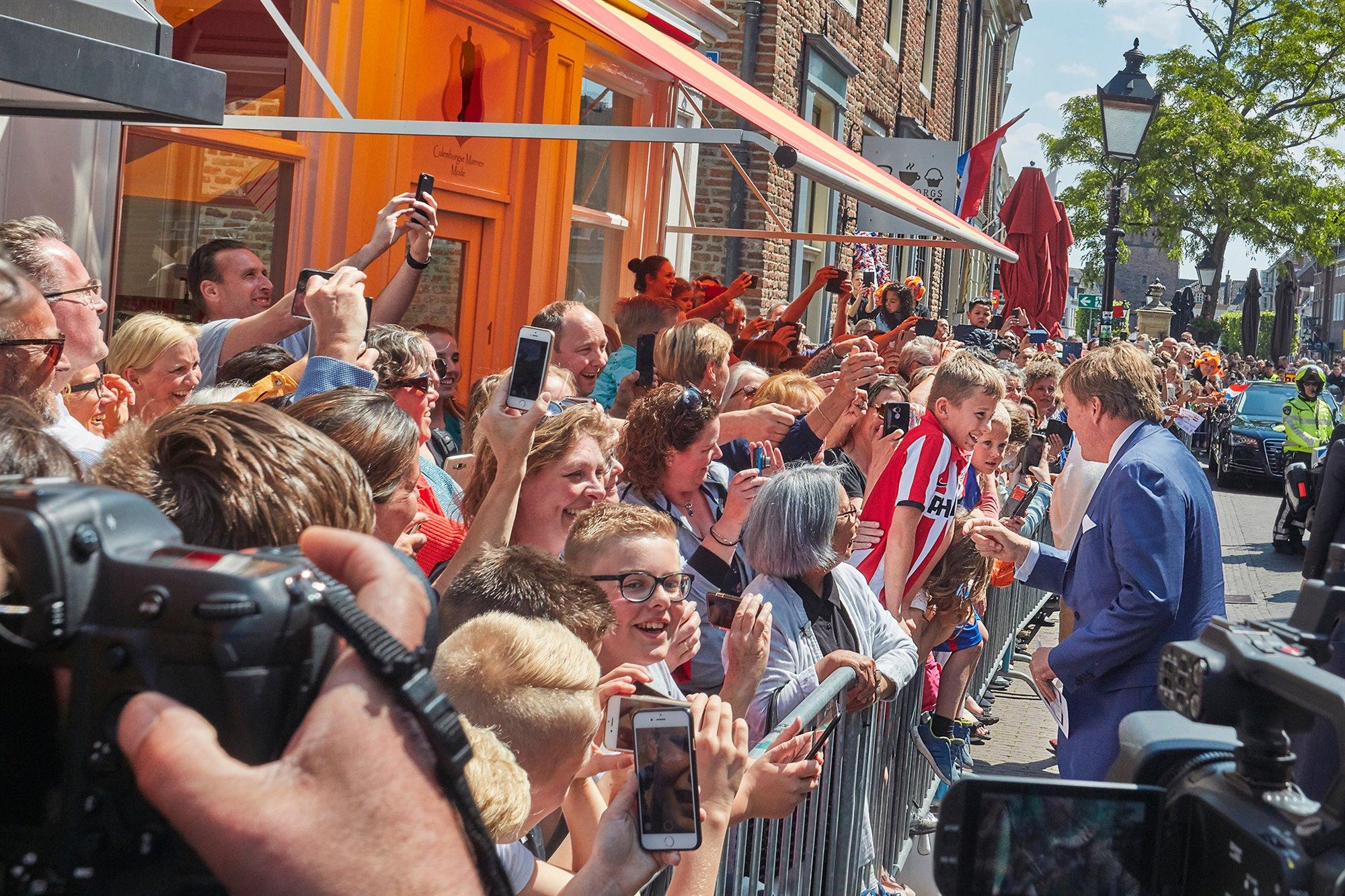 Koning Willem Alexander in gesprek met een van de vele kinderen langs de route. Veel vrolijke gezichten, blije kinderen voor een winkelpand, onder een zonnescherm achter dranghekken langs de looproute van het koninklijk paar. Verder zijn gebouwen, bomen, lantaarnpaal, motoragent, auto en camera's te zien.