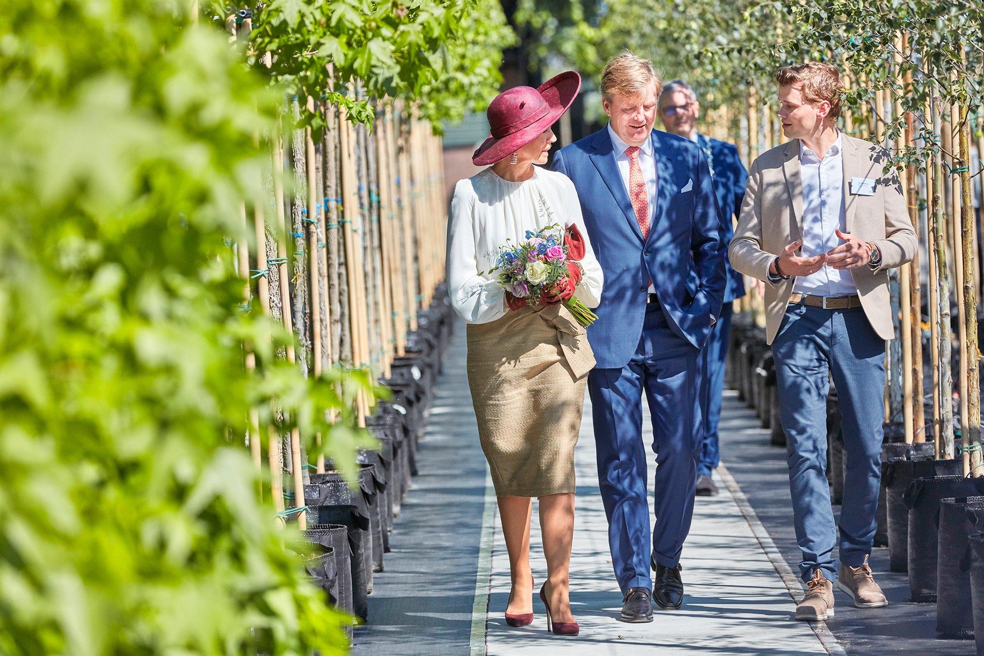 Koning en Koningin luisteren al wandelend tussen de bomenlaan naar een jonge medewerker.
