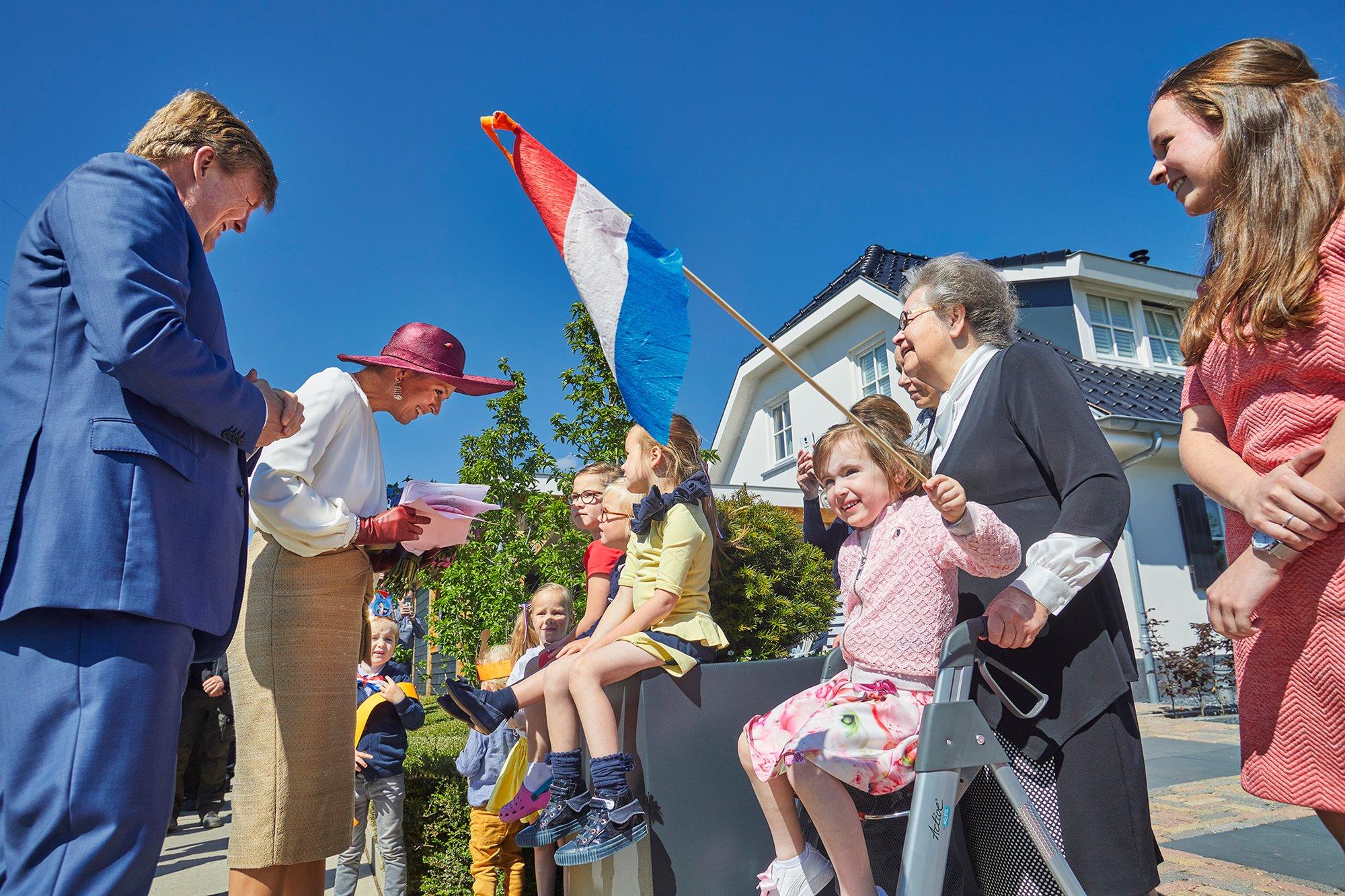 Kinderen langs de route, een meisje zwaait met de Nederlandse vlag, zittend op de rollator van haar oma, Koningin Maxima is in gesprek met enkele jonge kinderen, de Koning luistert mee. Vrolijke gezichte, zonnig tafereel. Op de achtergrond een woonhuis, struiken en een blauwe lucht.